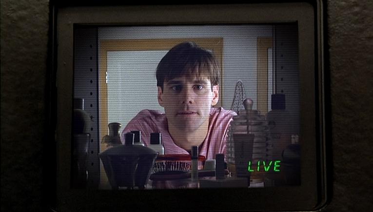 Truman parle à son reflet dans le miroir. Il ignore qu'une caméra est cachée derrière. <em>The Truman Show</em>, réalisé par Peter Weir, 1998